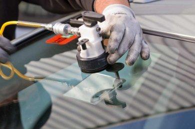 mechanic fixing car windshield