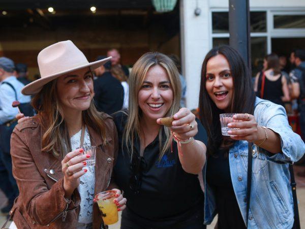 3 women holding shot glasses at event